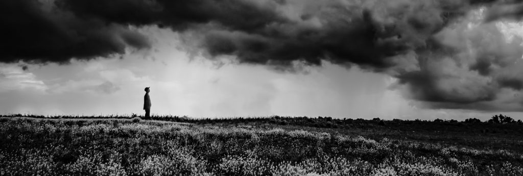 Selbst: Landwirt auf Feld schaut in Gewitterhimmel